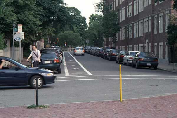 A cyclist and a motorist approach the blind corner at Concord Avenue and Follen Street